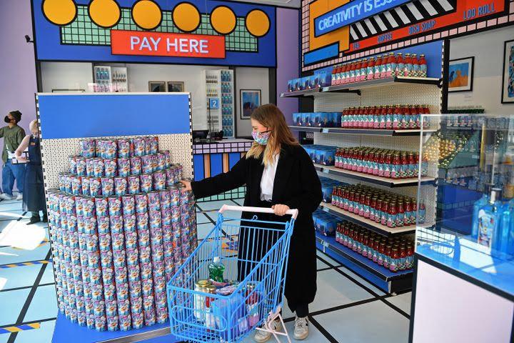 """Une cliente arpentant le """"premier supermarché au monde conçu par un artiste"""". (JUSTIN TALLIS / AFP)"""